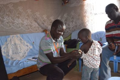 Community worker in Kenya measuring a small child's arm circumference