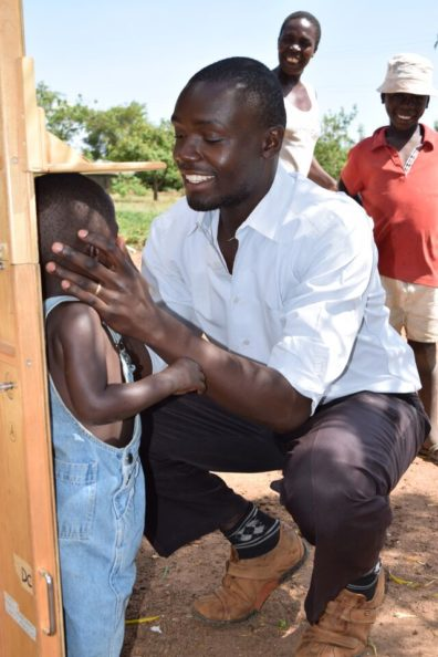 Community worker in Kenya measuring a small child's height