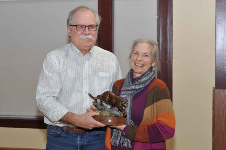 Kathleen Potter holding a cougar statue with Bryan Slinker