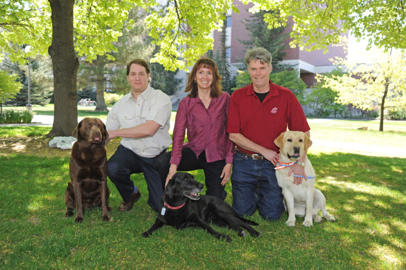 Nicolas Villarino with a chocolate lab, Katrina Mealey with a black lab, Michael Court with a yellow lab