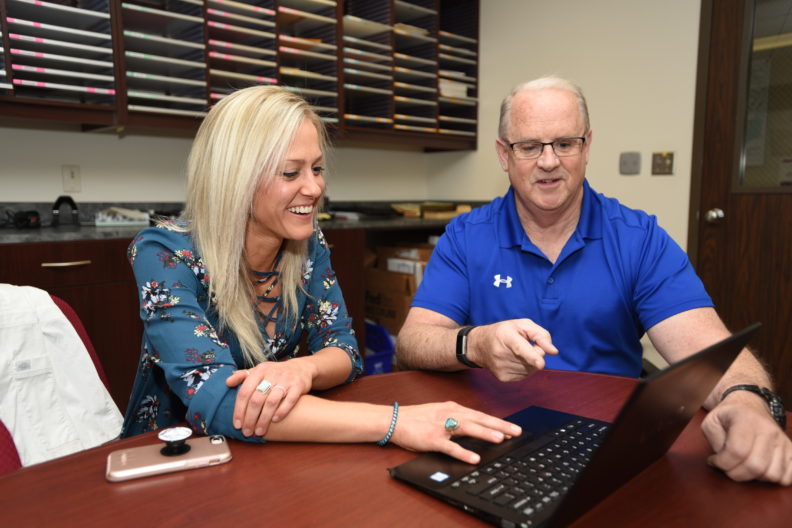 Rick DeBowes and Emily Thueson working at a computer