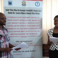 Eric Osoro and Hariet Mireiri in front of an informational sign on Zika
