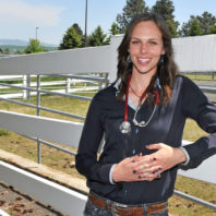 Haley Primley standing near a fence outside the veterinary teaching hospital