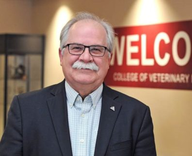 Dr. Slinker standing in front of a sign that says Welcome College of Veterinary Medicine