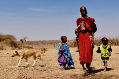 A Maasai woman walking with four children and a dog.