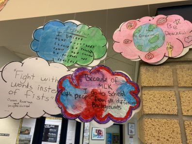 Mobile of paper clouds with students' writing
