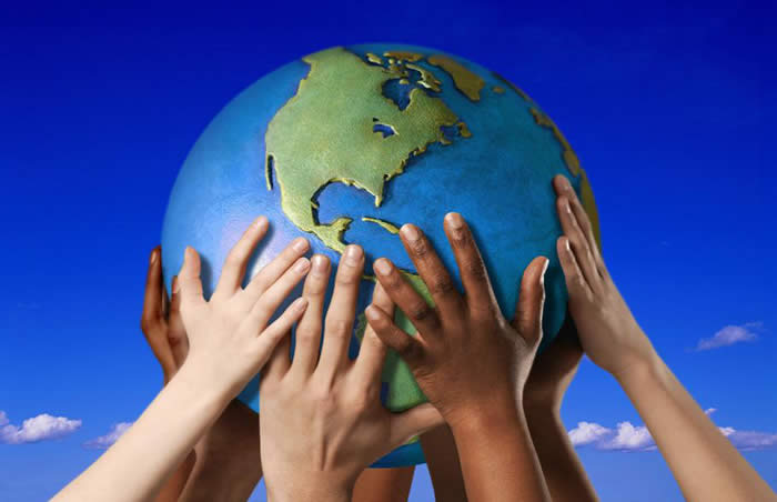 Many hands holding earth ball in blue sky