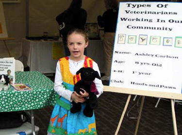 young girl, holding stuffed animal, giving a speech on types of veterinarians