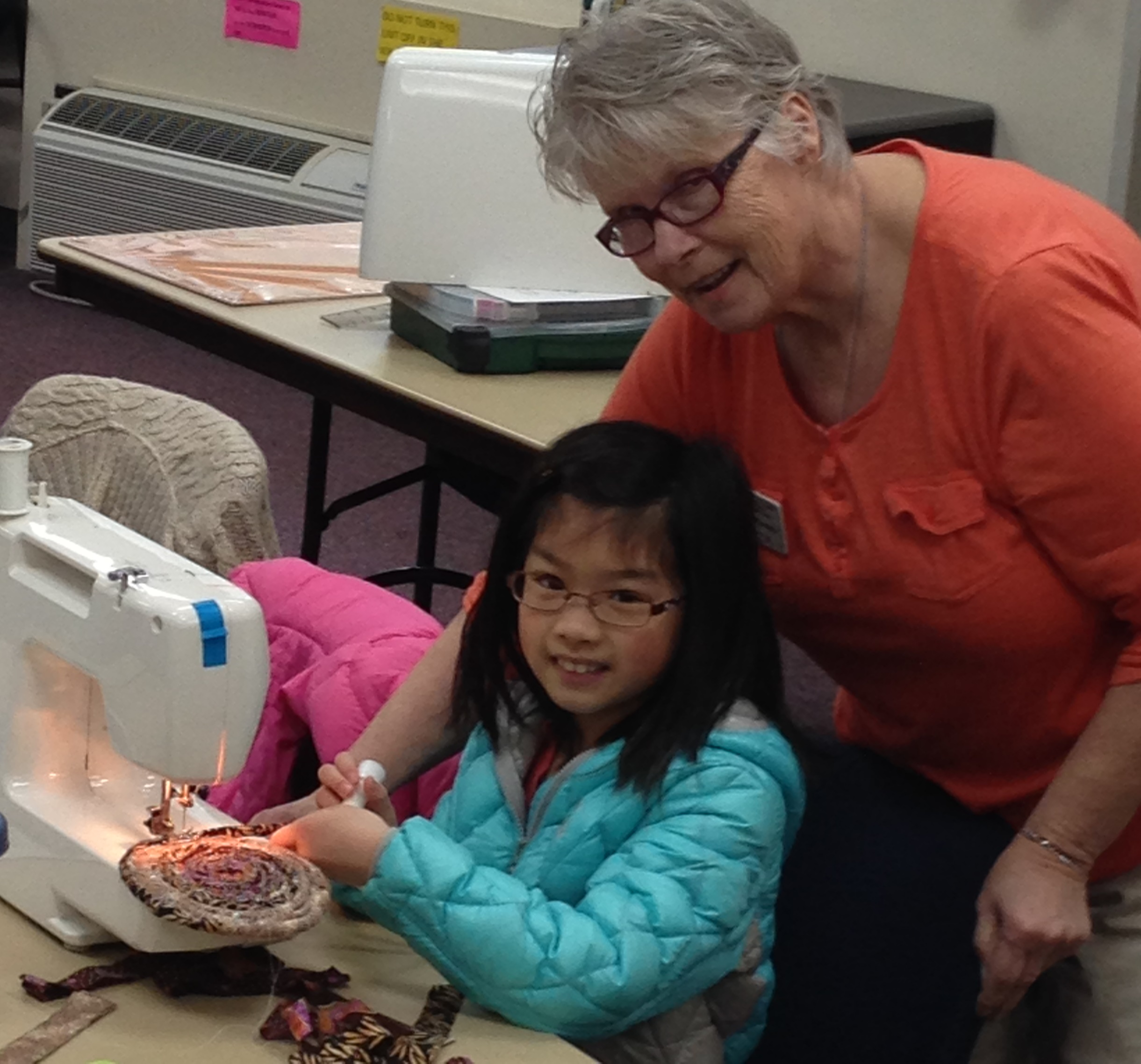 girl learning to sew, with adult mentor looking over her shoulder.