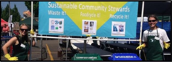 Two SCS volunteers at the county fair stand next to a sign on how to properly sort garbage placed behind two compostables and recycling bins.