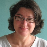 picture of a woman in white shirt with glasses, smiling