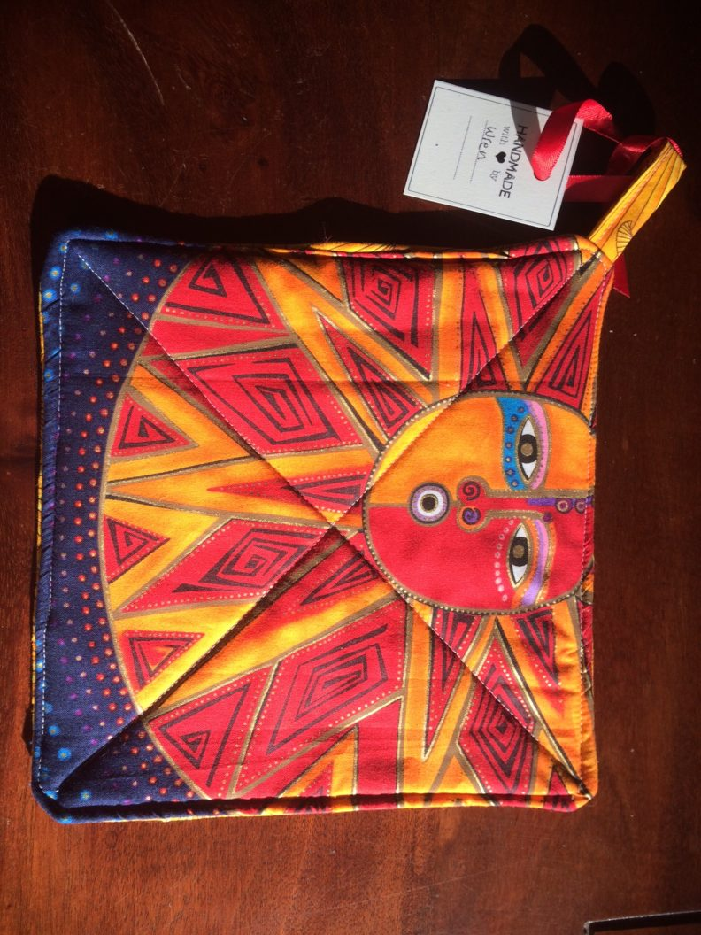 Potholder with orange and red art face and geometric patten fabric.