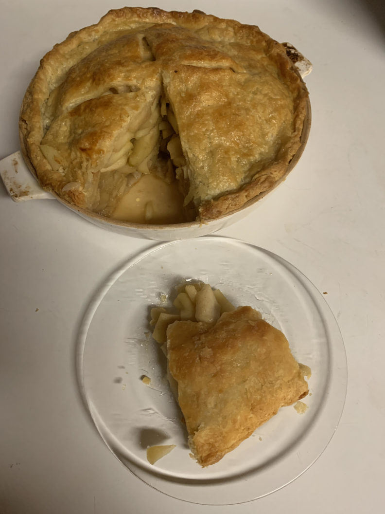 Apple pie with one slice put on a separate plate.