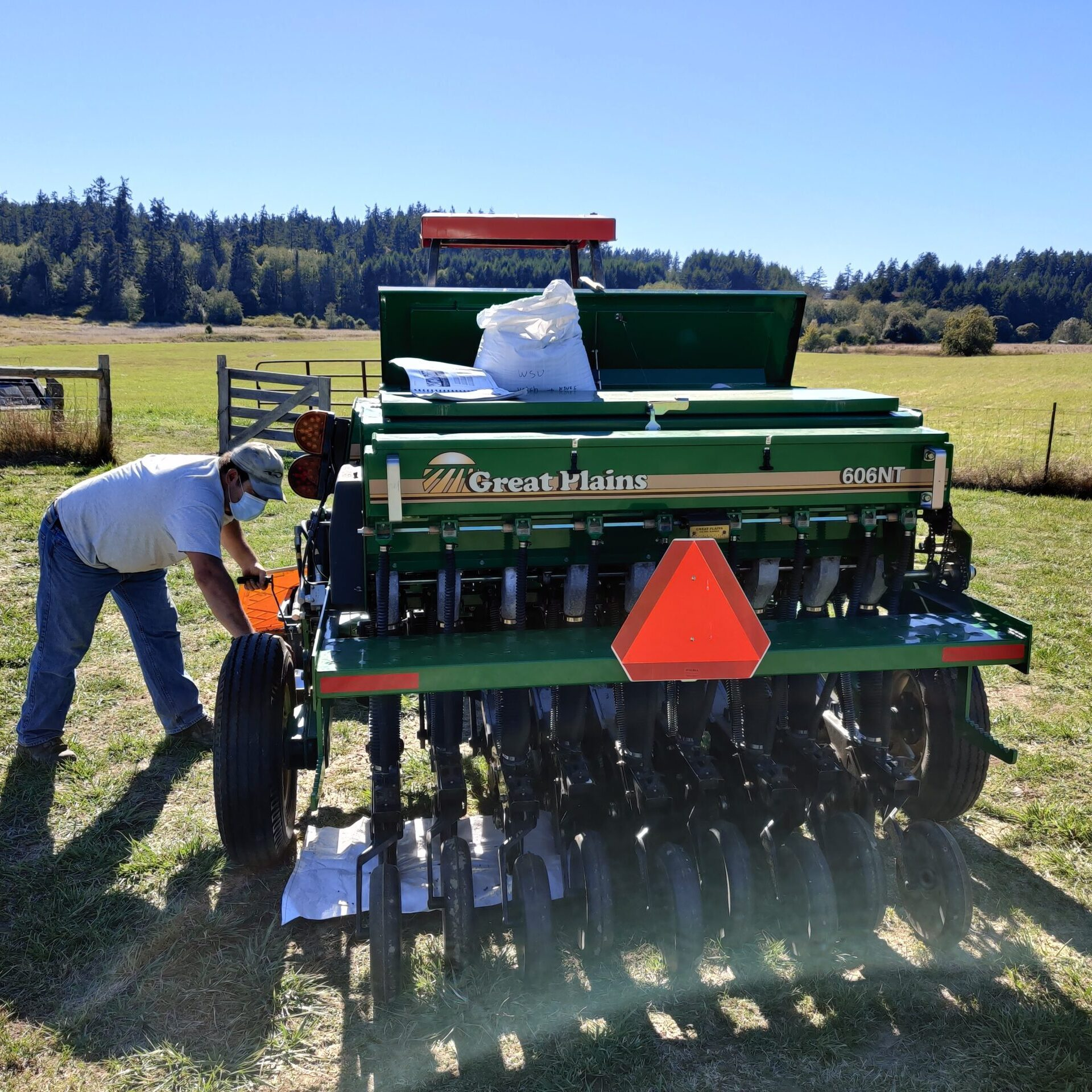 man in white tshirt and jeans leans over left side of no till drill