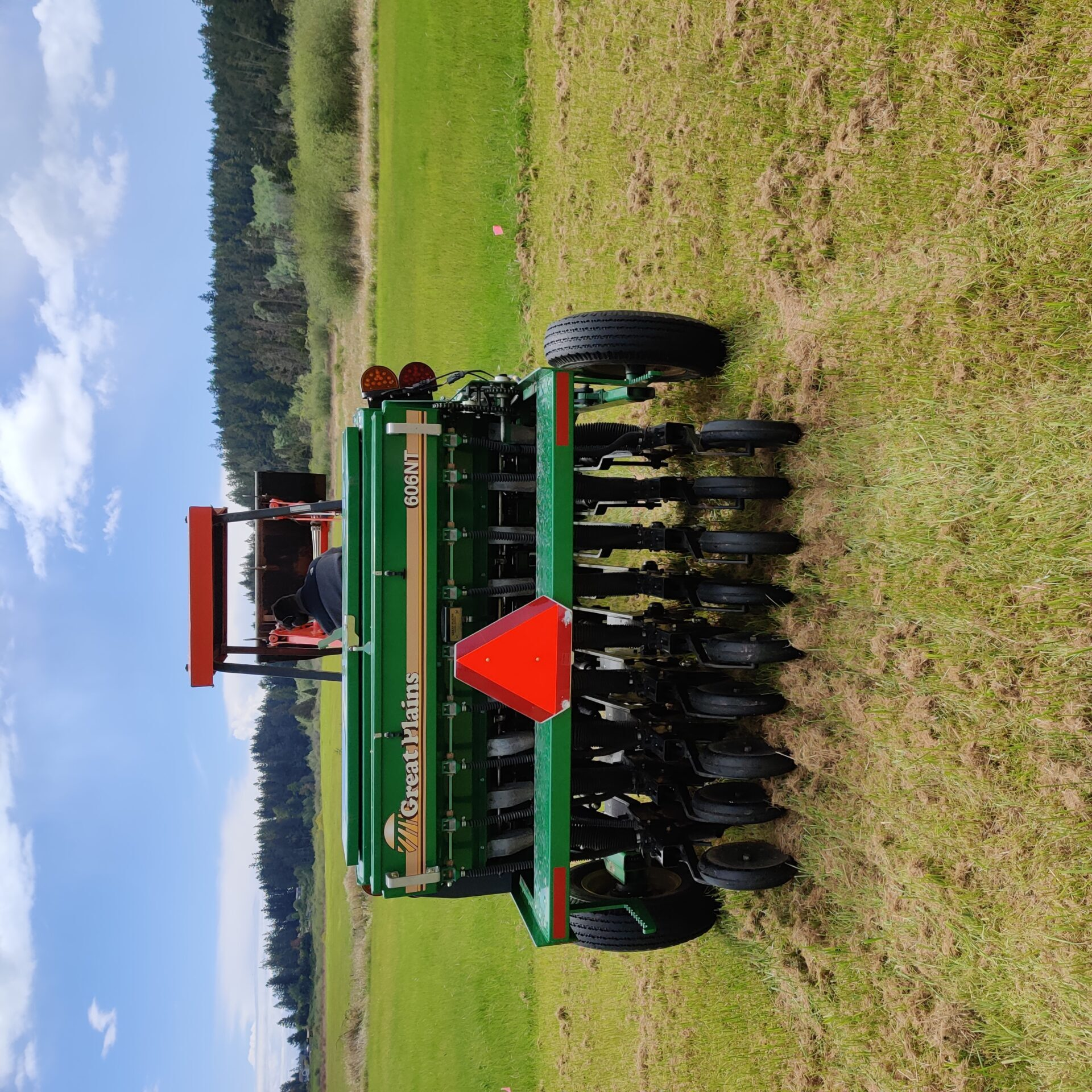 rear of no-till drill parked at the end of a freshly planted row in a pasture