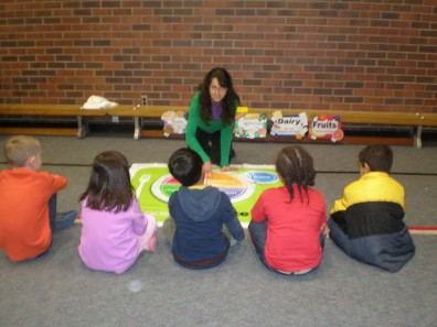 Candida Goza, Food $ense Educator, helps students remember there are 5 food groups in MyPlate.