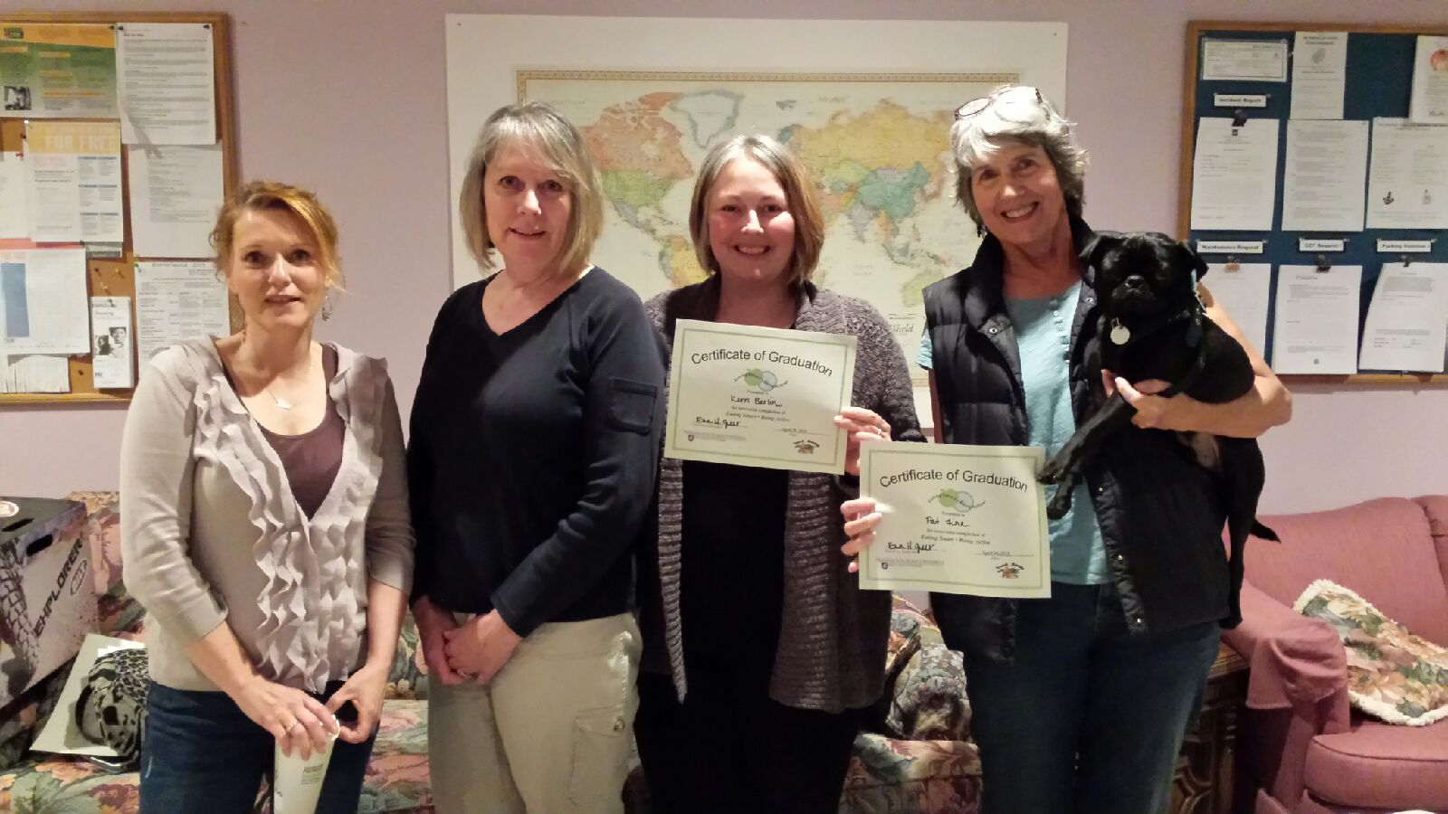 Graduates Monique, Kerri, and Pat show off their certificates with Adult Educator Erin and pup