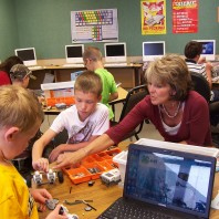 Teacher helping students with robotics