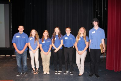 A group of youth in blue polo shirts stand on a stage