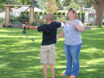 Boy shooting an arrow using a compound bow.