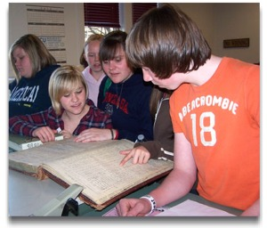 A group of youth examine a large, old, book.