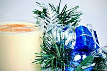 glass of eggnog next to holiday decorations
