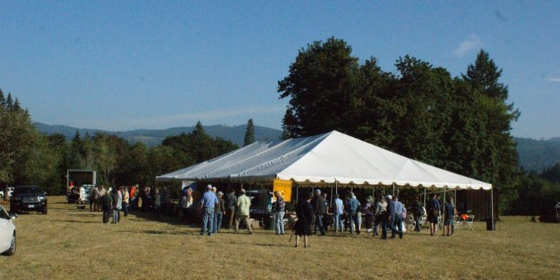 people crowded under tent in open field for forestry field day presentation
