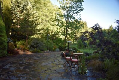 Flagstone patio with table and chairs with outside garden view