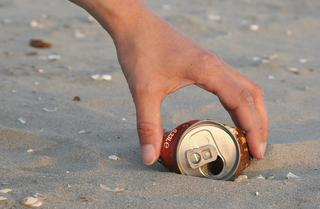 person_picking_up_litter_from_beach