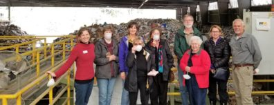 Waste Wise trainees standing before piles of unsorted recyclables at Cascade Recycling