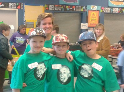 Three smiling boys in green shirts and colorful hats stand with their arms around each other.