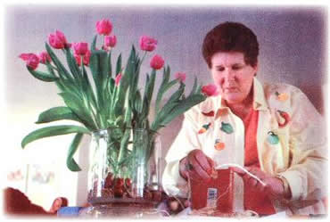 """Toni Caskey, a WSU Master Gardener, demonstrates separating """"daughters"""" from the mother bulbs."""