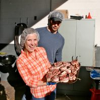 Two barbecue science students holding up a rack of chicken ready to grill