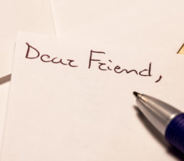 "A pen sits on a letter with ""Dear Friend"" written on it."