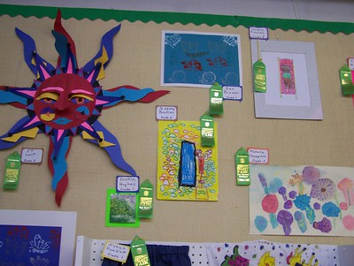 Several art pieces including drawings and a paper sun are hanging on a wall with ribbon awards
