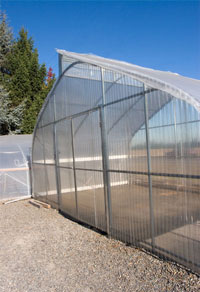 Lexan corrugated polycarbonate is used for the covering the end wall of this poly greenhouse. This type of covering offers impact strength, high light input, and durability.
