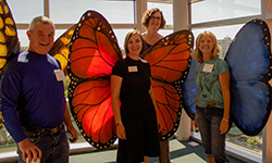 Three MGs wearing butterfly wings and MG coordinator, Erika Johnson.
