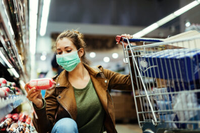 Young woman buying groceries while wearing face mask in the supermarket.