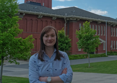 Assistant professor, Amelie Pedneault, smiling infront of Bryan Hall building.