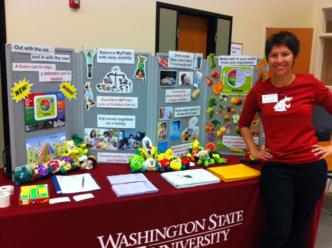Nutrition Education Assistant Holly Lacell in her Washington State University shirt manning a colorful booth full of nutrition facts, fruit and vegetable plushies, handouts, and stickers.