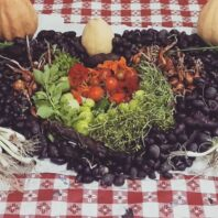 Potatoes, tomatoes, greens, herbs, and onions arranged in the shape of a colorful heart