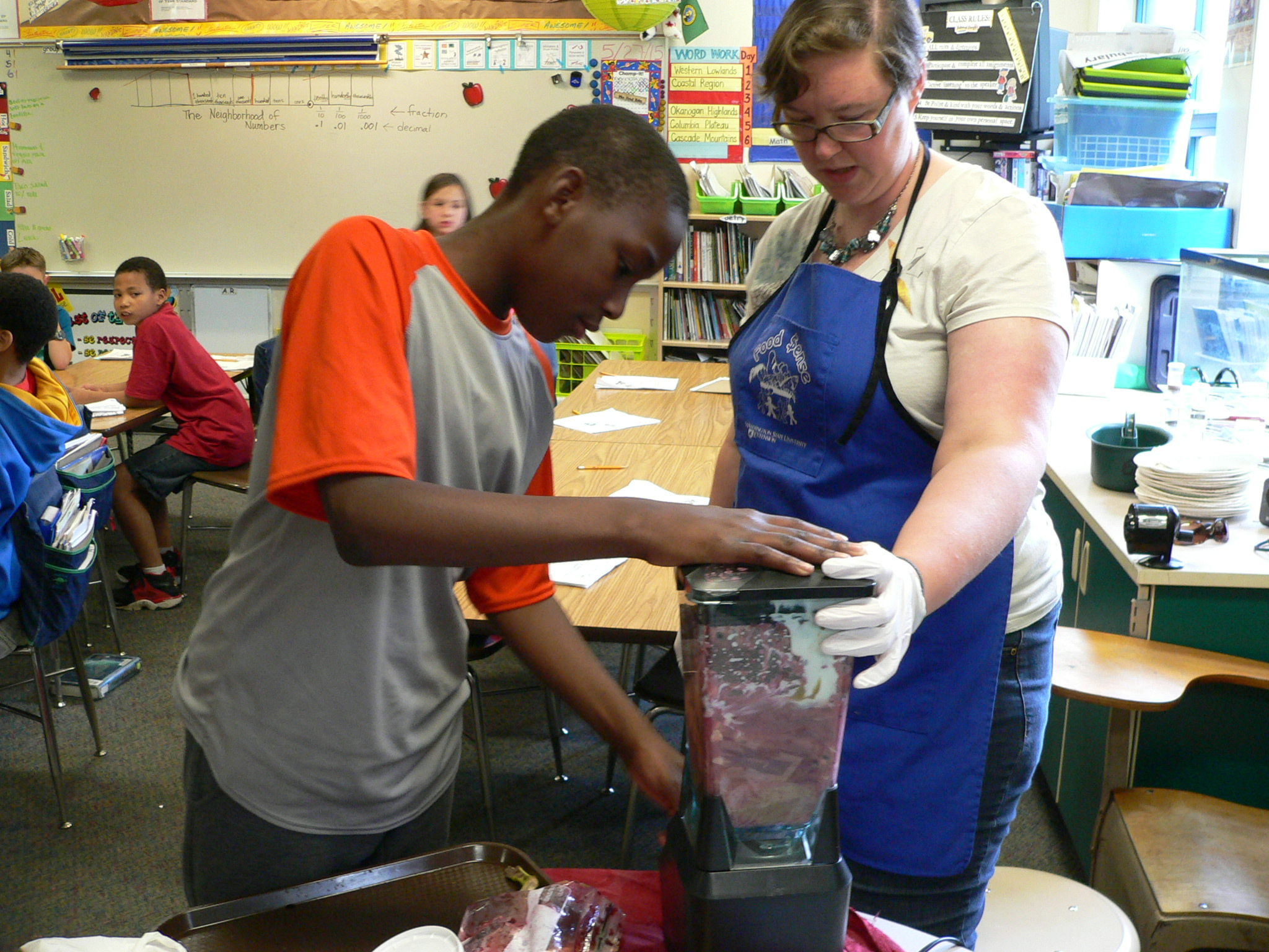 a European (white) nutrition educator blending a purple smoothie with an African-American (black) male youth