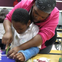middle aged black woman wearing pink jacket and bandana teaching her son how to chop an onion