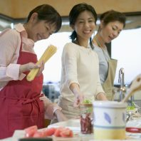 Asian ladies cooking with pasta smiling