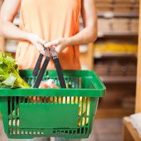 A European woman is holding a green plastic shopping cart
