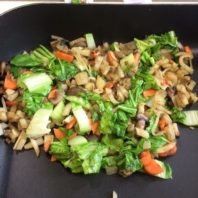leafy greens, carrots, onion, and potatoes cooked on an electric skillet