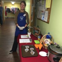 Tall white girl with blue aproan standing next to a food demonstration table