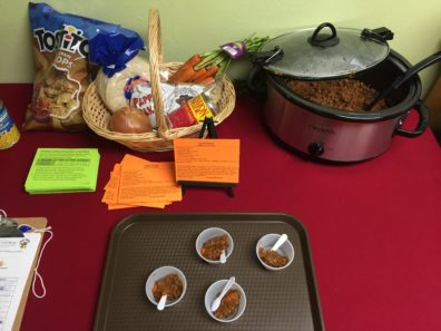 crockpot filled with lentil tacos on a red table with a display of smaples