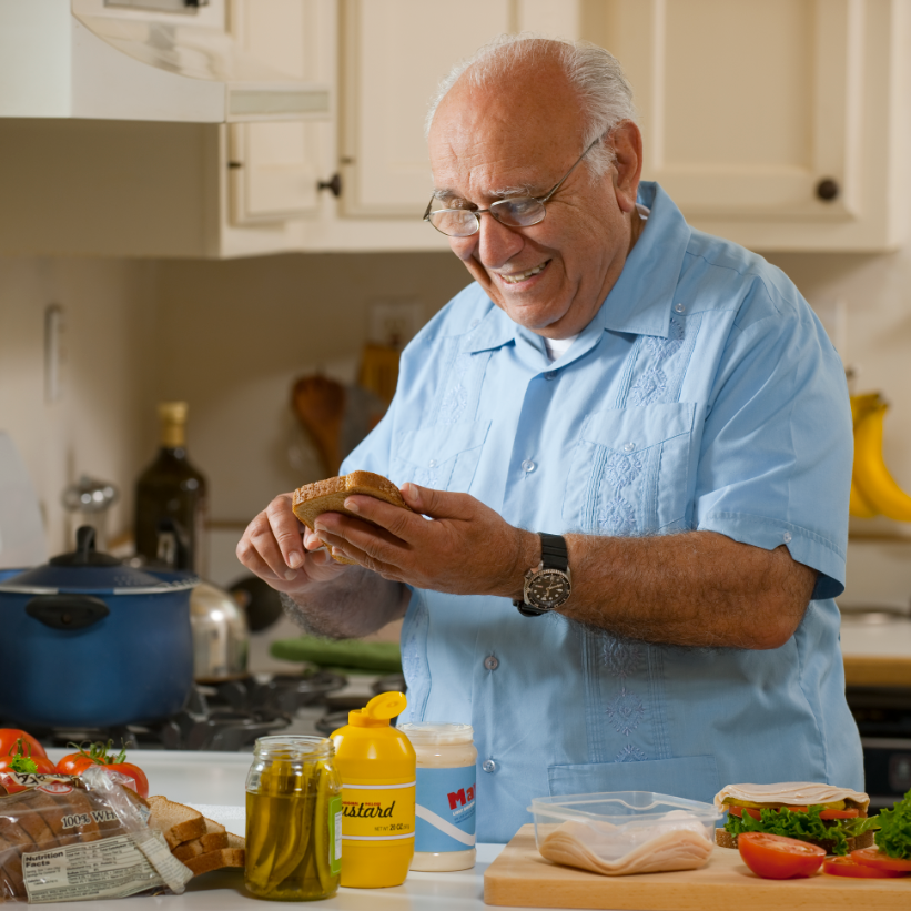 older European, Hispanic male making a sandwich in a home kitchen with white cabinets
