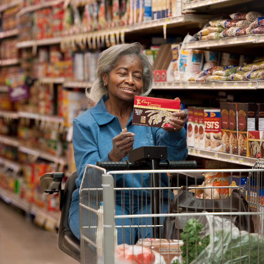 African female operating a motorized shopping cart to select foods at grocery store